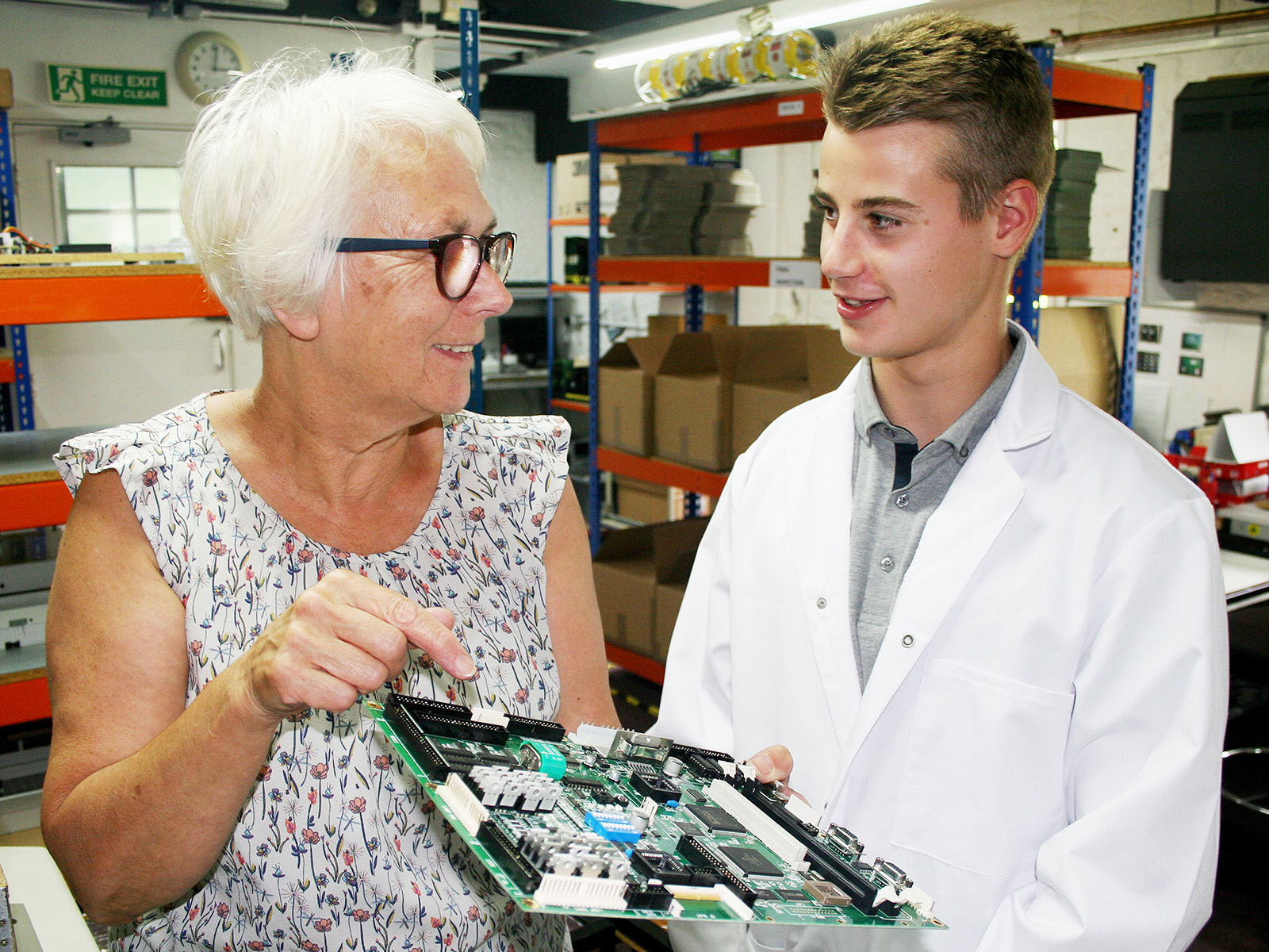 Cath Clark, Heber Production Controller (left) with Ben Latham (right) holding a Heber PCB